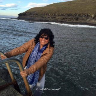 Inspirational photo of the Julia holding onto a ladder that leads to the ocean behind her. Breathtaking nature landscape combining a blight blue ocean with its waves hitting the green-brownish mountain in the far that touches the bright and light but sky with some white clouds. @JulliaFCardenasC